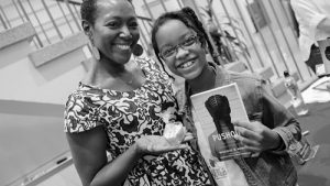 A picture of a black woman and a girl posing with the book Pushout.