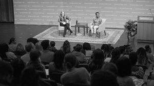 A black and white picture of a woman talking on a talk show or stage of some kind.