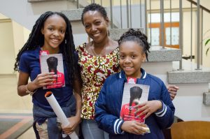 A black woman and two black girls posing with the PUSHOUT book.